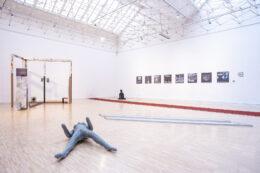 Zdjęcie przedstawia widok ogólny ekspozycji na dużej, górnej sali galerii. Na pierwszym planie leży popielata, gumowa lalka z sex-shopu. Tło stanowi parkiet na podłodze. W głębi, po lewej, stoi konstrukcja przypominająca z daleka ramy drzwi. Na ścianie po prawej stronie wiszą fotografie, a w głębi, tuż przy narożniku ustawiono tym razem siedzącą gumową lalkę.