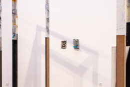 Zdjęcie przedstawia z bliska fragmenty konstrukcji widzianej z daleka na poprzedniej fotografii. Ramy z płyty pilśniowej w niektórych miejscach oklejone są rysunkami. W tle, na białej ścianie, wiszą dwa małe obrazki. Konstrukcja rzuca cień na ścianę.