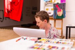 Tematem fotografii jest postać siedzącej w przestrzeni wystawy portrecistki – młodej kobiety o krótkich włosach i jasnej cerze. Przed nią, na pierwszym planie, rozłożone są pudełka z kolorowymi pastelami, których używa do wykonywania portretów. Kobieta zwrócona jest profilem, patrzy na trzymany przez siebie blok rysunkowy.