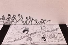 Dolną połowę fotografii zajmuje leżący arkusz z czarno-białym komiksem, ułożony na czarnym tle. Za nim, na białej ścianie, narysowano czarnym pisakiem pnące się kształty przypominające kiełkujące rośliny.