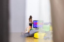 """Na pierwszym planie wiszą częściowo rozsunięte półprzejrzyste kotary, za którymi widać postać dziewczyny stojącej tyłem do widza, przed ekranem telewizora. Obok, na podłodze leży kolorowa sterta rozmaitych przedmiotów. Na wspomnianym ekranie wyświetlane są duże napisy, z których przeczytać można słowo: """"RAZEM""""."""