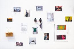 Zdjęcie przedstawia widok białej ściany, na której zawieszono liczne, kolorowe prace niedużych rozmiarów. Wśród nich są m.in.: mała drewniana półka, arkusz papieru z wydrukowanym tekstem i kolorowe fotografie.