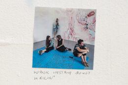 """Fotografia przedstawia kolorowe, kwadratowe zdjęcie umieszczone na białej ścianie górnej sali galerii. Na zdjęciu przedstawione są cztery młode osoby: trzy siedzące na podłodze dziewczyny i stojący za nimi, w głębi kadru, chłopak z aparatem fotograficznym. Pod tą fotografią, bezpośrednio na ścianie, napisano kredką: Widok wystawy """"Pokój w ruchu""""."""