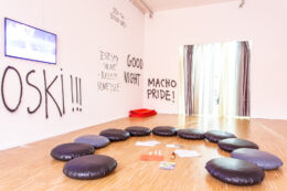"""Zdjęcie przedstawia fragment ekspozycji. W pustej sali widzimy czarne, okrągłe, skórzane poduszki do siedzenia, ułożone w niepełnym kręgu na parkiecie. Jest to miejsce przeznaczone do wspólnych spotkań i działań. Wokół bezpośrednio na ścianach wykonano sprejem czarne napisy, np. """"JESTEŚMY SILNE – RAZEM SILNIEJSZE""""."""
