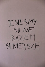 """Zdjęcie przedstawia czarny napis wykonany grubym markerem na białej ścianie, o treści: """"JESTEŚMY SILNE – RAZEM SILNIEJSZE""""."""