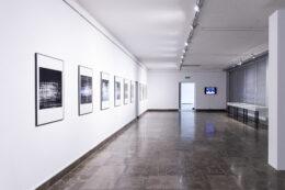 Fotografia prezentuje widok ogólny wystawy. Na białej ścianie po lewej stronie zawieszone są oprawione fotografie. W głębi, na wprost, znajdują się otwarte drzwi prowadzące do holu oraz ekran z projekcją filmu zawieszony na ścianie przy oknie. Po prawej stronie, wzdłuż zakrytych roletami okien, stoją gabloty na cienkich czarnych nogach.