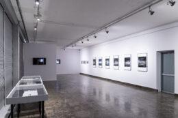 Fotografia prezentuje kolejne ujęcie wystawy. Po lewej stronie, wzdłuż zasłoniętych roletami okien, stoją gabloty, w głębi znajdują się dwa ekrany z projekcjami, a na długiej białej ścianie po prawej wiszą oprawione, czarno-białe fotografie w większych i mniejszych formatach. Sporą część kadru zajmuje szara, wzorzysta podłoga.
