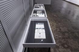 Tematem zdjęcia są te same trzy gabloty, fotografowane z góry – tak że wyeksponowana jest ich zawartość. Są to przede wszystkim otwarte książki i inne publikacje. Po prawej stronie kadru rozciąga się szara, wzorzysta podłoga.