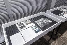 Zdjęcie przedstawia dwie z trzech wspominanych wcześniej gablot. Ich zawartość stanowią książki i inne publikacje otwarte do czytania. Na większości kartek oprócz tekstów wydrukowane są fotografie. Publikacje leżą na czarnym tle, ściany gablot są białe.