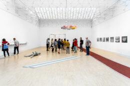 Zdjęcie przedstawia dużą grupę ludzi na wystawie podczas oprowadzania kuratorskiego. Stoją na środku sali. Jednej z osób towarzyszy mały piesek. Z boku, po lewej stronie osobno stoją dwie inne osoby. Wszyscy, których twarze widać, mają maseczki.