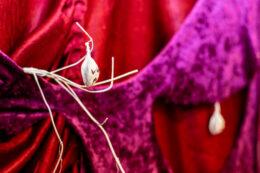 Fotografia przedstawia mały fragment znacznie większej pracy wykonanej z drapowanych tkanin. Całość jest dużą zawieszoną na drążku kotarą. Fragment składa się z dwóch tkanin – wiśniowej i fioletowej. Do draperii przyczepiono małe białe przedmioty, jeden z nich przypomina gałązki. Na jednej z nich wisi mała zawieszka w kształcie główki, o narysowanej symbolicznie smutnej twarzy.
