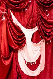 Zdjęcie przedstawia kolejny fragment kotary skonstruowanej z drapowanych tkanin. Główny materiał, stanowiący tło, ma kolor wiśniowy, a zawieszona na nim tkanina jest bladoróżowa. W niektórych miejscach do draperii przyczepiono małe zawieszki, w większości w kolorze białym.