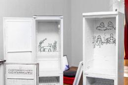 Fotografia przedstawia dwie otwarte, puste lodówki, bez półek i fragment trzeciej. Na ich wewnętrznych, tylnych ścianach widnieją rysunki wykonane czarnym mazakiem. Pierwszy od lewej przedstawia bliżej nieokreślone uśmiechnięte zwierzę wśród kilku rachitycznych roślin, a drugi rodzajową scenkę podglądania dwóch kobiet przez ukrytych za nimi dwóch mężczyzn.
