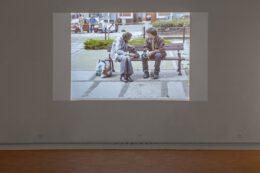 Tematem fotografii jest slajd będący częścią pracy Franciszka Orłowskiego. Slajd wyświetlany jest w wyciemnionej sali. Przedstawia scenę, w której artysta rozmawia z bezdomnym. Obaj mężczyźni siedzą na ławce, zwróceni do siebie twarzami.