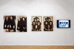 Zdjęcie przedstawia prace Izabelli Gustowskiej, wyeksponowane na białej ścianie galerii. Są to, od lewej, 4 grafiki i ekran z projekcją wideo. Zarówno grafiki, jak i wideo przedstawia różne konfiguracje postaci kobiet będących bliźniaczkami. Dominuje czarno-biała kolorystyka, ale na dwóch grafikach doczepione są różowe detale z tkaniny.